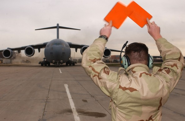 A crew chief guides in a C-17A Globemaster III at Khashi-Karanabad air base in Uzbekistan on Dec. 16 2005. (U.S. Air Force photo by Staff Sgt. Steven Pearsall)