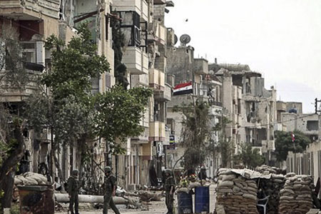 Syrian soldiers patrolling a destroyed Homs neighbourhood. Photo FreedomHouse on Flickr