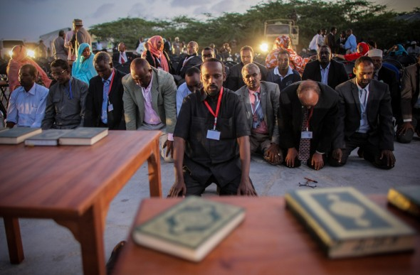 New MPs pray during the inauguration ceremony for members of Somalia's first parliament in twenty years. (Photo: AU-UN IST/Stuart Price)