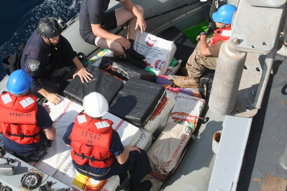 Navy and Coast Guard personnel come alongside USS Nicholas to transfer contraband.